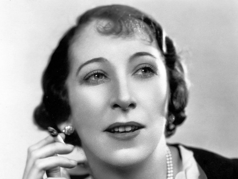 Photograph of British actress, Martita Hunt (1). The actress wears pearls while smoking a cigarette
