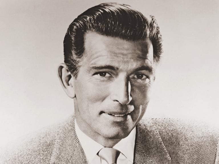 Photography of Michael Rennie, British actor, wearing a jacket and tie