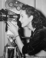 Patricia Roc behind the camera for a change, takes a look through the view finder to observe the scene from her fiance Andre Thomas's viewpoint – he is an expert French cameraman.    They will be married in the spring of this year.  An off-set shot from The Perfect Woman, the Two Cities film version of the successful comedy, starring Patricia Roc with Stanley Holloway and Nigel Patrick, produced by George and Alfred Black and directed by Bernard Knowles at Denham.