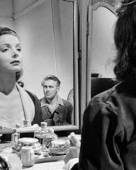 Fay Lowther (Elizabeth Sellars) at her dressing table is watched by Supt Bob Lowther (John McCallum) in a scene from The Long Memory (1953)