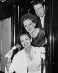 The premiere of the latest Kenneth More comedy Next to No Time will be held on the world's greatest liner Queen Elizabeth at Southampton, and the film loads were taken by special train from Waterloo today.  Much of the film is shot aboard the liner.  Photo shows: Top to bottom: John Gregson, Phyllis Calvert and Janette Scott leave for the premiere.