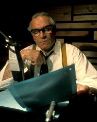 Photo of Laurence Oliver narrating The World at War (1973-4). The actor is in rolled-up shirt sleeves while reading the script in front of a microphone