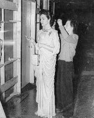 Margaret Lockwood smokes while she undergoes the finishing touches to her costume in Look Before You Love.