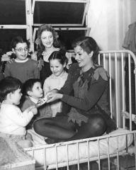 Margaret Lockwood, in costume as Peter Pan, perches on a bed in the ward and laughs as she plays with the children at London's Great Ormond Street Hospital in 1949