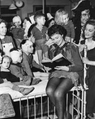 Margaret Lockwood, in costume as Peter Pan, perches on a bed in the ward as she reads to the children at the Great Ormond Street Hospital in 1949