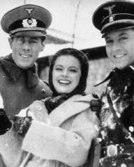 Margaret Lockwood plays with a snowball during a break from filming Night Train to Munich.   Rex Harrison and Paul Henreid look on.