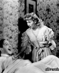 Roland Culver (Richard Halton) sits up in bed in On Approval as Googie Withers (Helen Hale) looks on