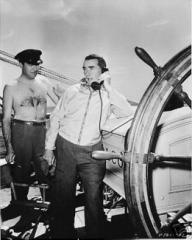 Frank Lloyd cuts an anachronistic figure as he takes a telephone call during the filming of Rulers of the Sea