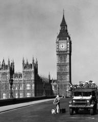 A deserted Westminster bridge and Big Ben form the background as an army truck stops a woman and her dog out during curfew.  A scene from Seven Days to Noon (1950)
