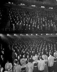 The cast and audience of Strike a new Note at the Prince of Wales Theatre, London, sing 'The King' at the close of every public function. (February, 1944)