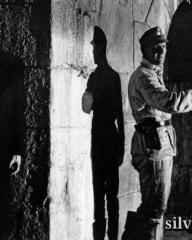 Orson Welles (Harry Lime) hides behind a wall from armed guards in The Third Man