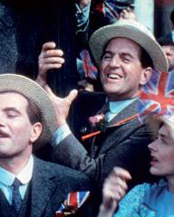 Colour photo from This Happy Breed (1944) featuring people in a crowd waving Union Jacks