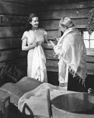 Shura (Lily Kann), the Russian house-keeper, prepares a Finnish steam bath for Lucy Glover (Margaret Lockwood) and asks her to get ready