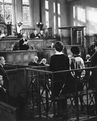 The counsel asks Lottie Smith (Joan Greenwood) whether she pleads 'guilty' or 'not guilty' to the attempted murder of her baby. (2)
