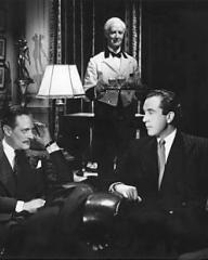 In the lounge of the St. James Club, Fobey (Guy Middleton) tells Dick Glover (Dennis Price) that he thinks he is seeing too much of Lucy Templar
