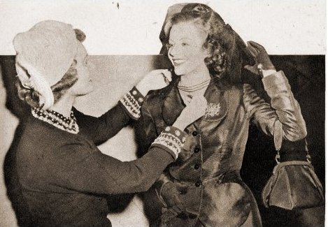 Off the set of Trent's Last Case, Anna Neagle helps Margaret Lockwood with her costume.