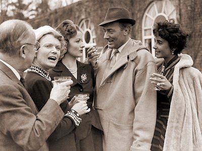 Margaret Lockwood and Michael Wilding toast on the set of Trent's Last Case.  Also enjoying the occasion are producer Herbert Wilcox and British actress Anna Neagle, along with Wilding's wife Elizabeth Taylor.