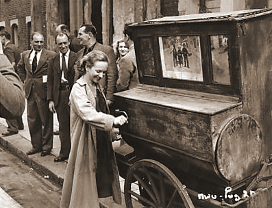 Joan Greenwood, one of the stars of The White Unicorn, amuses herself with an old barrel organ while on location in Hammersmith for shots of a dockland city.    Joan plays the role of Lottie, a slum girl who never has a real chance in life
