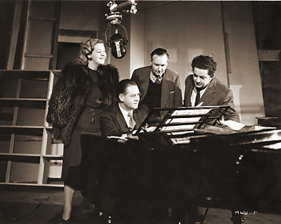 Bretton Byrd, Musical Director of The White Unicorn, plays one of his tunes for recording.    Kyra Vayne, Russian singer, Reg Wyer, (Lighting Cameraman) and Bernard Knowles (Director) look on