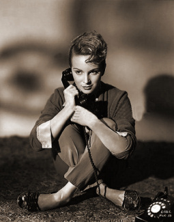 Joan Greenwood as Sabina Pennant in Young Wives' Tale sits cross-legged on the floor and takes a telephone call